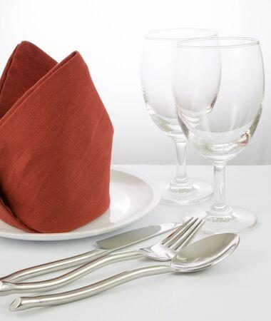 fork glasses: fork and knife on red napkin and wine glasses
