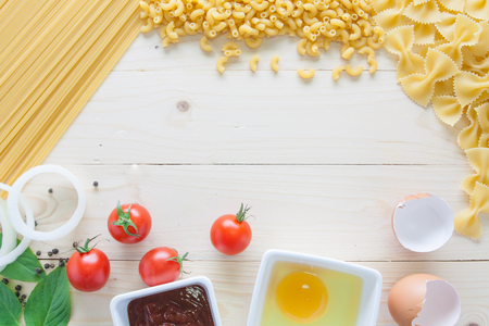 spaghetti with ingredients for cooking on wood background top view flat