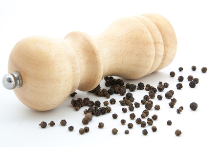 pepperbox: pepper mill of wood with peppercorns and ground pepper Stock Photo