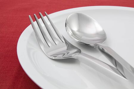 plate with fork and knife on red tablecloth Stock Photo