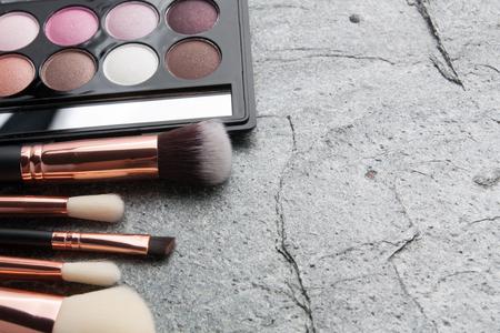 Vários produtos de maquiagem em fundo escuro com copyspace