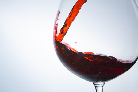 wine being pouring into a glass closeup wine splashing splash Stock Photo