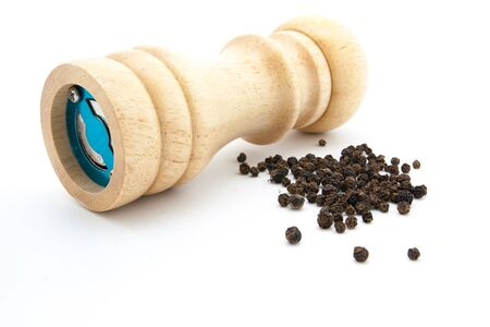pepper mill of wood with peppercorns and ground pepper Stock Photo
