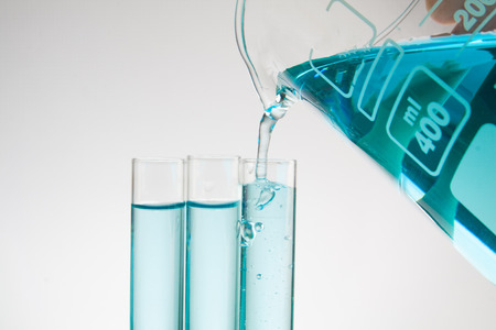 Science pipette with a pour of substance over laboratory test tubes Stock Photo