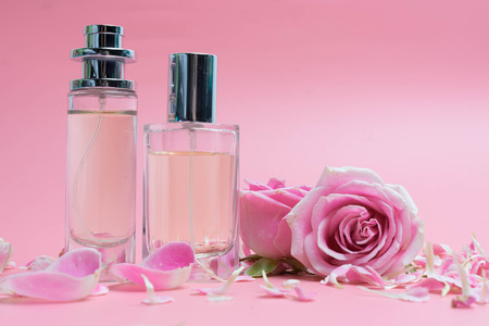 Beautiful perfume bottles and rose on pink Stock Photo