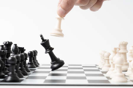 hand businessman moving chess on a chessboard