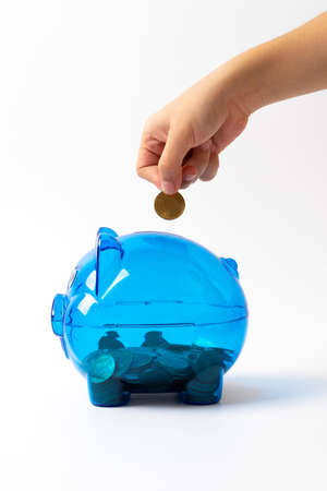 blue piggy bank hand putting coin into on white background