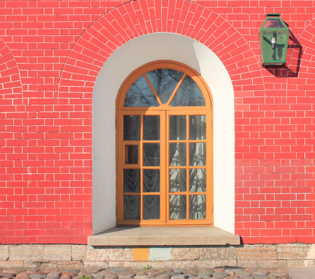 Brick House Arch Window on Wall and Small Lantern Lamp. Old Vintage Classic House Facade with Vibrant Bright Red Brick Stone Wall Texture at Cobblestone Narrow Street on Summer Bright Day Image.