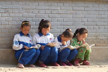 illiteracy: Julio de 2011, el condado de Qingshui, provincia de Gansu: cuatro estudiantes de primaria leyendo libros contra la pared Editorial