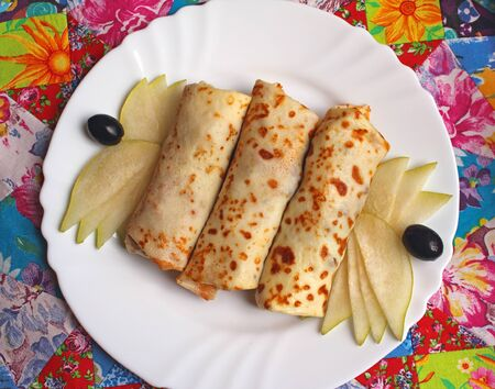Stuffed crepes and pear slices on a plate  Stock Photo - 18903186