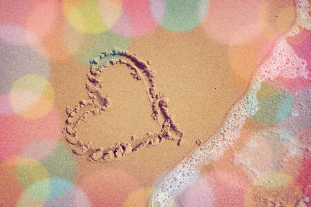 Heart on the sea sand. Vintage background with place for inscriptions. photo