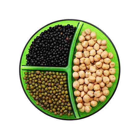 Three species of legumes: chick-pea, mung bean and black lentils on a platter. Isolated on white background. photo
