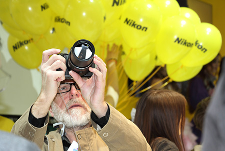 enthusiastically: Moscow, Russia - April 12, 2015: International Exhibition of photography.Forum professionals and photography enthusiasts. Visitor enthusiastically studying camera.