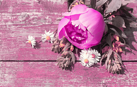 art processing: Summer background with wildflowers and peonies on an old table. Space for text. Art processing in lilac shades.