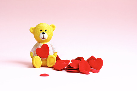 Teddy bear and a lot of hearts on a pink background. Background for valentine or wedding cards. Stock Photo