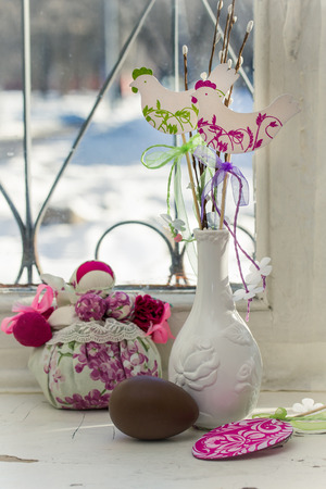 crack willow: Easter still life in retro style. Chocolate egg, rag doll and a vase on a windowsill. Easter decoration. Sunny spring day. Stock Photo