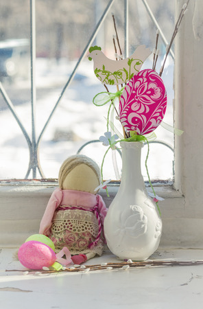 crack willow: Easter decoration on the windowsill. Easter still life in retro style. Rag Doll and a vase with decorations. Stock Photo