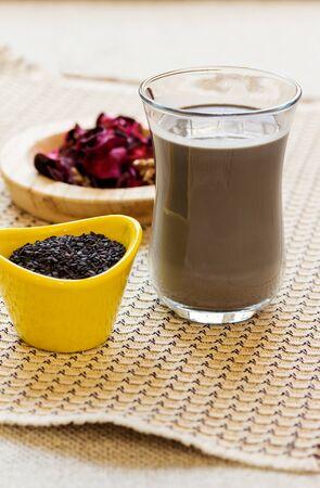 Black sesame milk and black sesame seeds. Sesame seed milk in a glass. Vertical shot.
