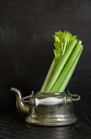 threadbare: Dark food background with old metal kettle and fresh celery. Vintage food background. Lots of copy space. Stock Photo