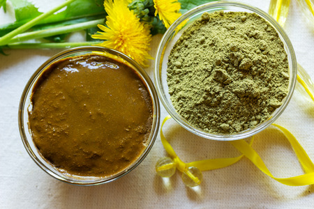 Henna powder. Henna paste. Prepare the henna paste at home. Still life with henna and dandelions. Focus on the powder. Stock Photo