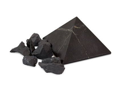 Pyramid and pieces shungite mineral on white background. Shungite Pyramid Mineral. Pyramid made of natural shungite.