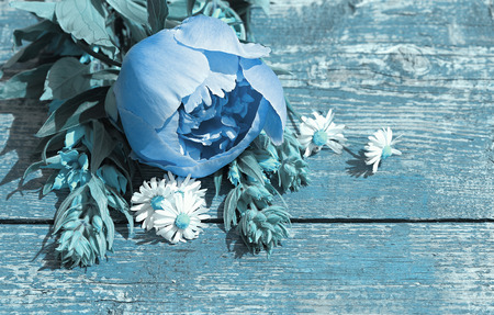 art processing: Summer background with wildflowers and peonies on an old table. Space for text. Art processing in a blue tint.