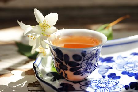 Tea tray and jasmine flowers. Cup of tea and jasmine flowers. Tea still life. Soft focus. Stock Photo