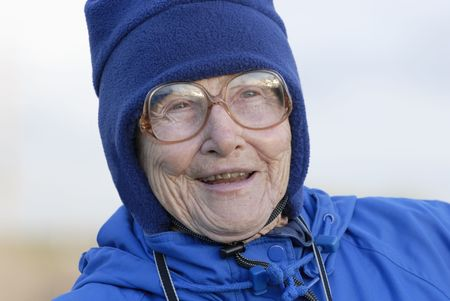 An old woman, bundled in a warm hat and jacket, stares off into the distance. Stock Photo