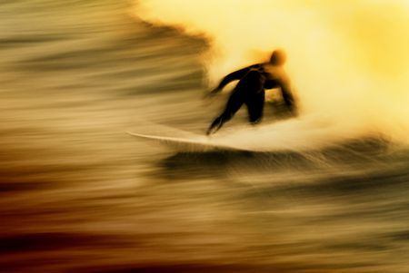 Long exposure of a surfer at sunset. Has a grunge like feel with the rider appearing to ride out of flames.