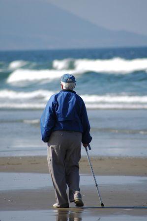 Am elderly person strolls down the beach alone.