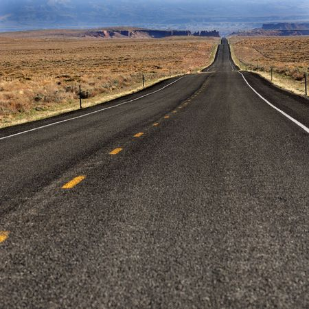 across: A road in the southwest USA across the hot desert.
