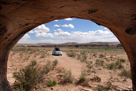 An automobile and desert landscape viewed from a cave in Americas beautiful southwestern desert near the San Juan River, Arizona.