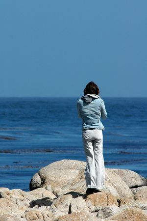 A young woman stands alone looking out into the Pacific ocean. Stock Photo
