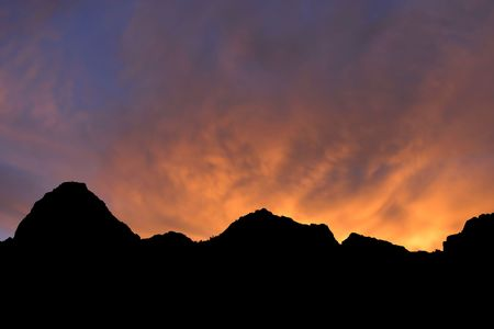 A fire orange and red sunrise silhouettes the mountains of Zion National Park, Utah, USA.