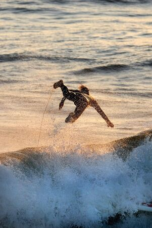 glint: A silhouette of a surfer flying through the air. Stock Photo