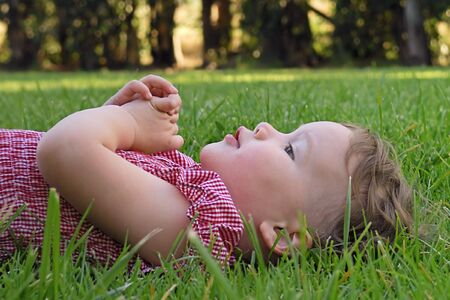 innocense: A young girl lies down in the grass and rests her hands on her chest after a long afternoon of playing at the park.