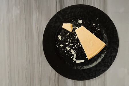parmesan cheese: Block of fresh parmesan cheese on a black plate Stock Photo