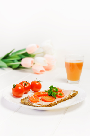 light breakfast: Fresh light breakfast made of brown bread with ham and tomatoes