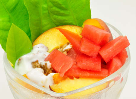 musli: Fruit cup with watermelon, peaches, musli and green leaves Stock Photo