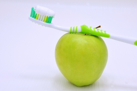 Small green apple and white toothbrush with toothpaste