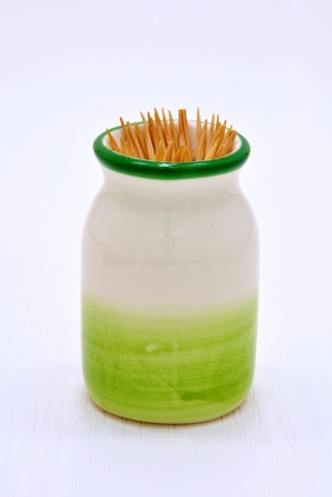 Small green ceramic bowl with many wooden toothpicks photo