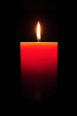 Burning large orange candle on a black background photo
