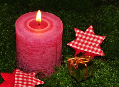 Burning Christmas candle on moss with a gift and stars Stock Photo - 14985714