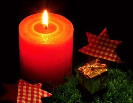 Burning Christmas candle on moss with a gift and stars photo