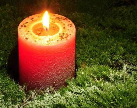 Burning Christmas candle on the snow - covered moss