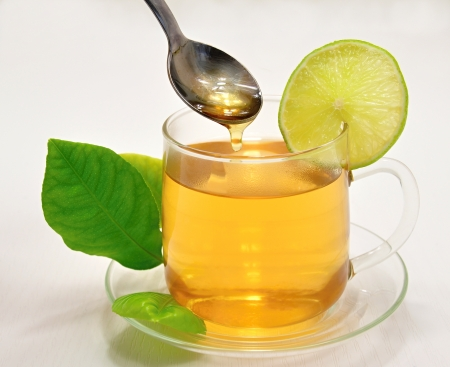 Glass cup of hot lemon tea with a slice of lemon and honey Stock Photo