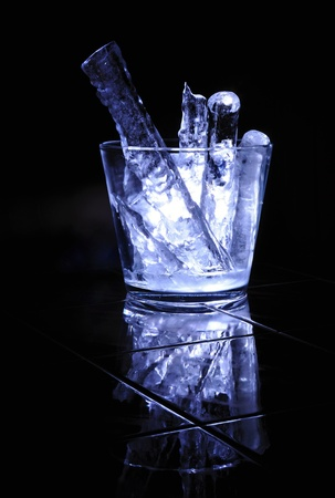 Large pieces of ice in a glass jar on a black background