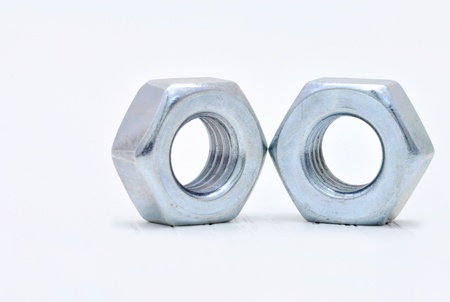 Two galvanized steel nuts on a white background photo