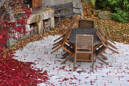 Autumn garden with old wooden furniture covered by leaves photo
