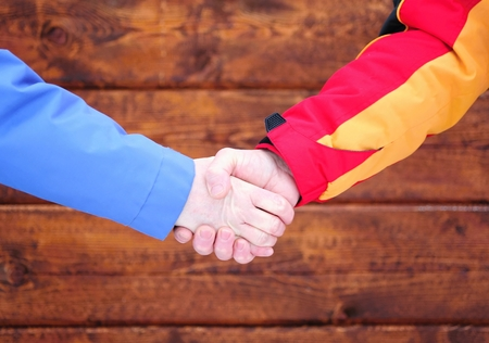 Business handshake before the new brown wooden building photo